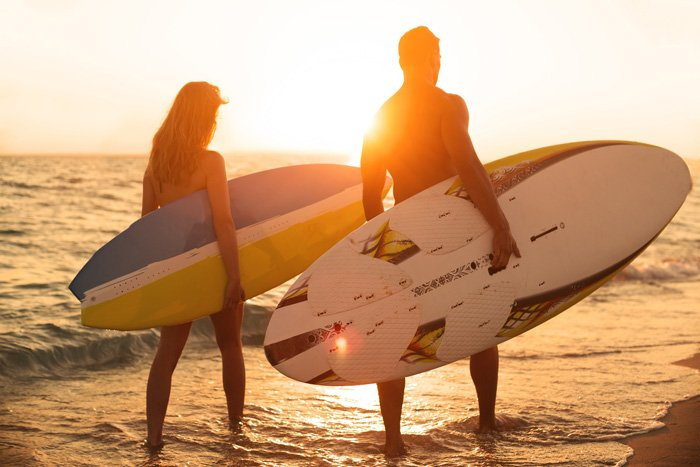 Couple on the beach holding their boards.